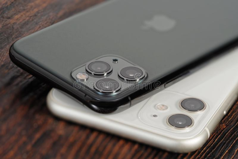 White iPhone 11 and space gray iPhone 11 Pro. Koszalin, Poland – December 02, 2019: White iPhone 11 and space gray iPhone 11 Pro. The iPhone 11 and royalty free stock images