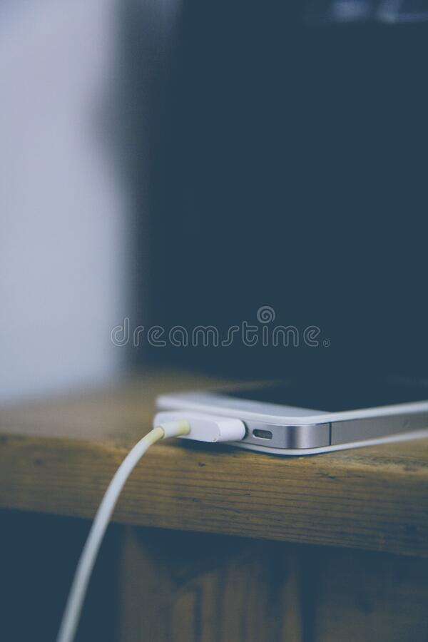 White Iphone 4 at Top of Brown Table stock images