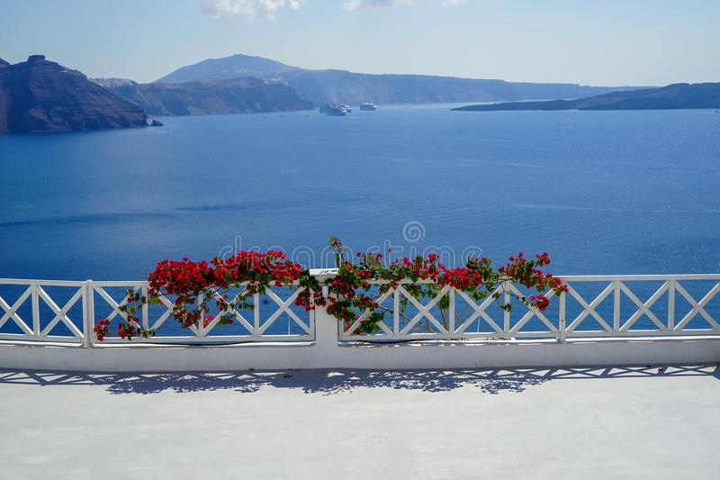 White island balcony with dark pink red Bougainvillea flower foreground in front of scenic mediterranean sea view and caldera stock photo