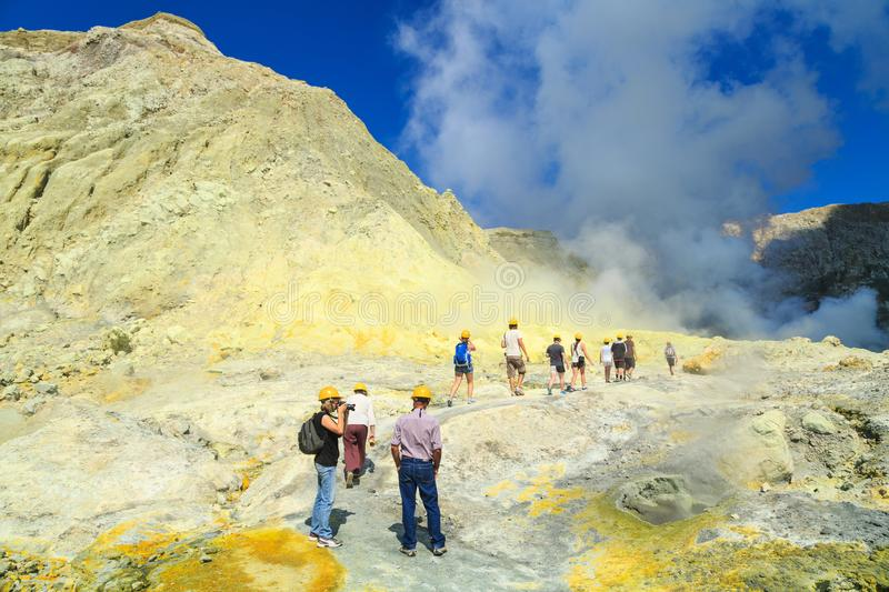 White Island, New Zealand. Tourists walking toward the crater lake. Tourists wearing safety helmets move through the dramatic landscape of White Island, an stock photo
