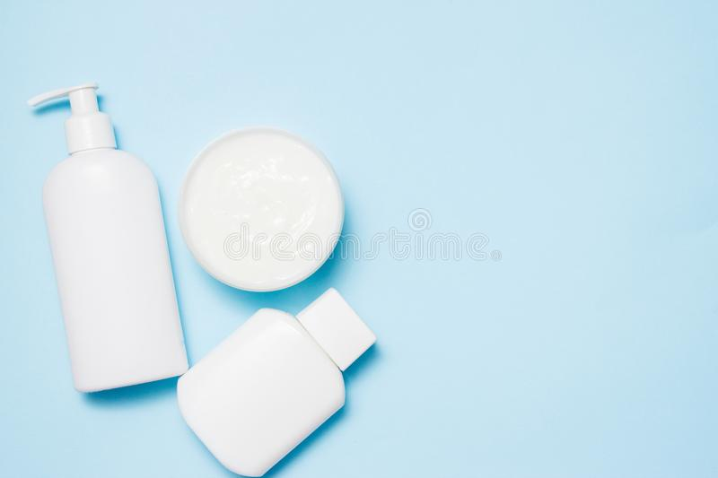 White jars of cosmetics on a blue background. Bath accessories. Face and body care concept.  royalty free stock images
