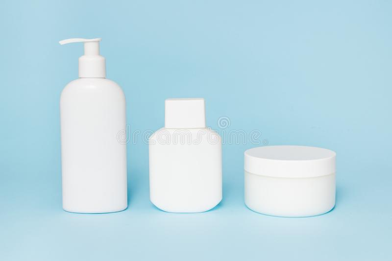 White jars of cosmetics on a blue background. Bath accessories. Face and body care concept.  royalty free stock photos