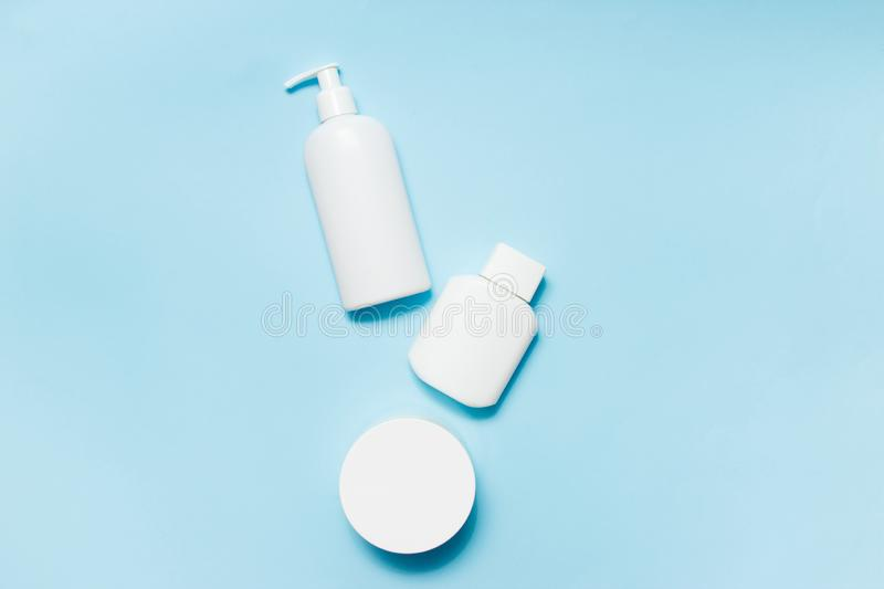 White jars of cosmetics on a blue background. Bath accessories. Face and body care concept.  stock photography