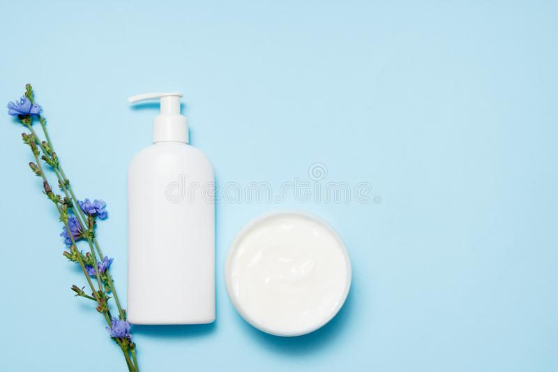 White jars of cosmetics with flowers on a blue background. Bath accessories. Face and body care concept. Top view.  royalty free stock photography