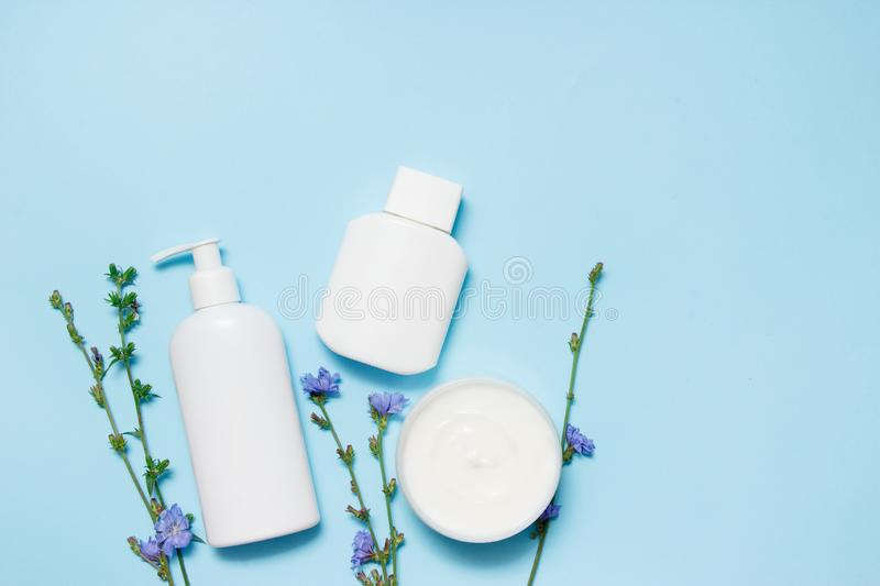White jars of cosmetics with flowers on a blue background. Bath accessories. Face and body care concept. Top view.  stock photo