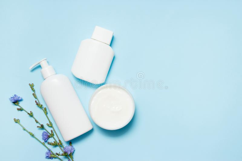White jars of cosmetics with flowers on a blue background. Bath accessories. Face and body care concept. Top view.  royalty free stock image