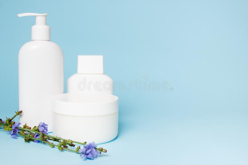 White jars of cosmetics with flowers on a blue background. Bath accessories. Face and body care concept.  royalty free stock photo
