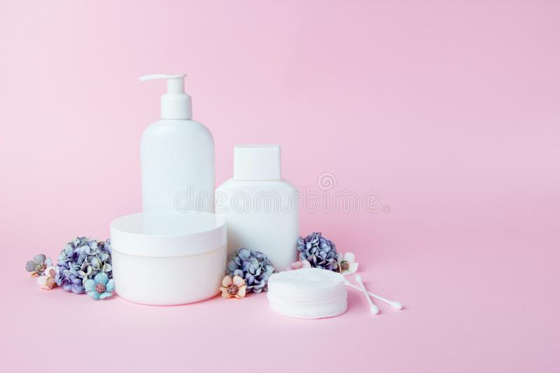 White jars of cosmetics with flowers on a pink background. Bath accessories. Face and body care concept.  stock photography