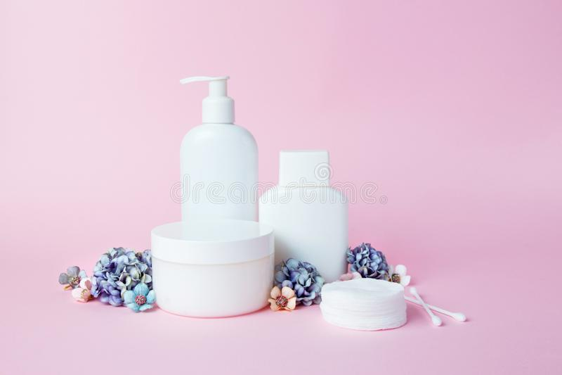 White jars of cosmetics with flowers on a pink background. Bath accessories. Face and body care concept.  stock photo
