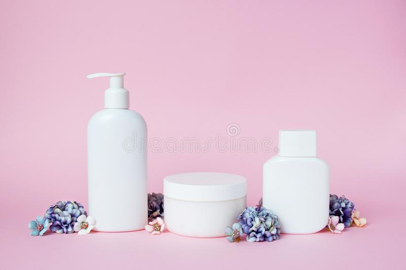 White jars of cosmetics with flowers on a pink background. Bath accessories. Face and body care concept.  stock image
