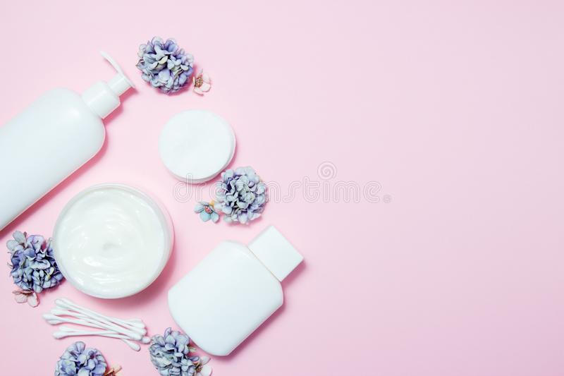 White jars of cosmetics with flowers on a pink background. Bath accessories. Face and body care concept. Top view.  stock photography