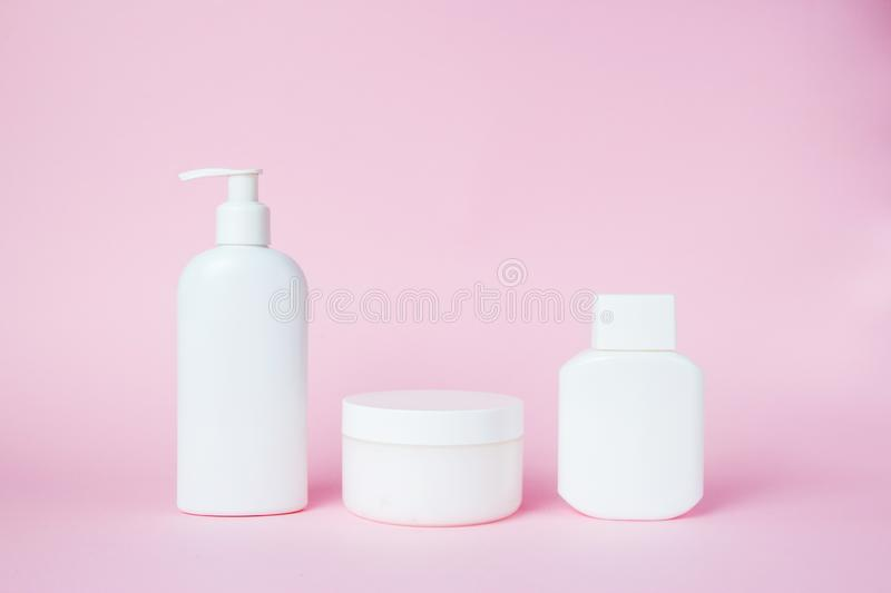 White jars of cosmetics on a pink background. Bath accessories. Face and body care concept.  royalty free stock photo