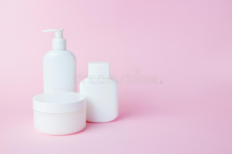 White jars of cosmetics on a pink background. Bath accessories. Face and body care concept.  stock photography