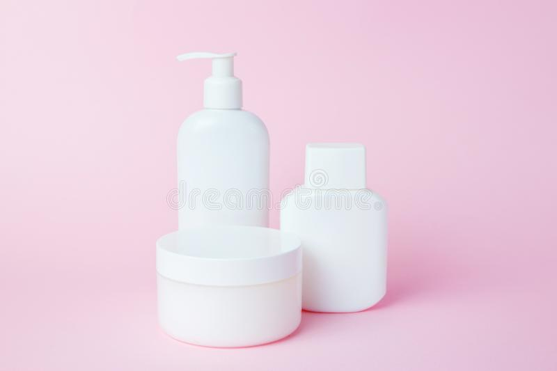 White jars of cosmetics on a pink background. Bath accessories. Face and body care concept.  stock image