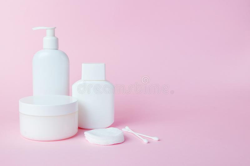 White jars of cosmetics on a pink background. Bath accessories. Face and body care concept.  royalty free stock photos