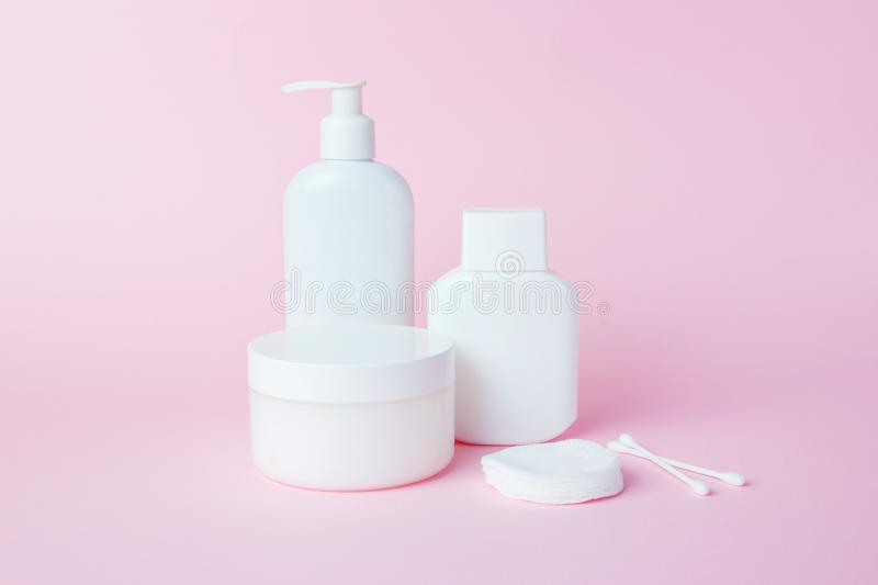 White jars of cosmetics on a pink background. Bath accessories. Face and body care concept.  stock images