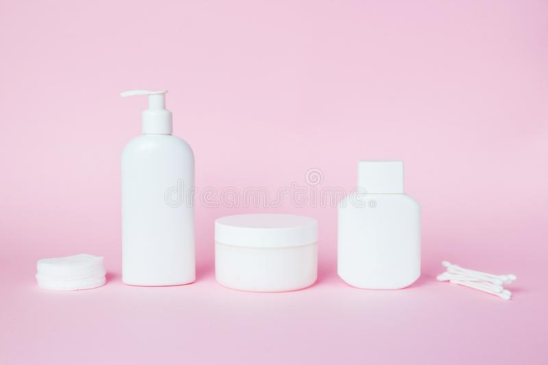 White jars of cosmetics on a pink background. Bath accessories. Face and body care concept.  stock photos