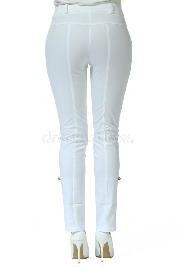 White jeans trousers on model legs with white stiletto heels. With bare toes stock images