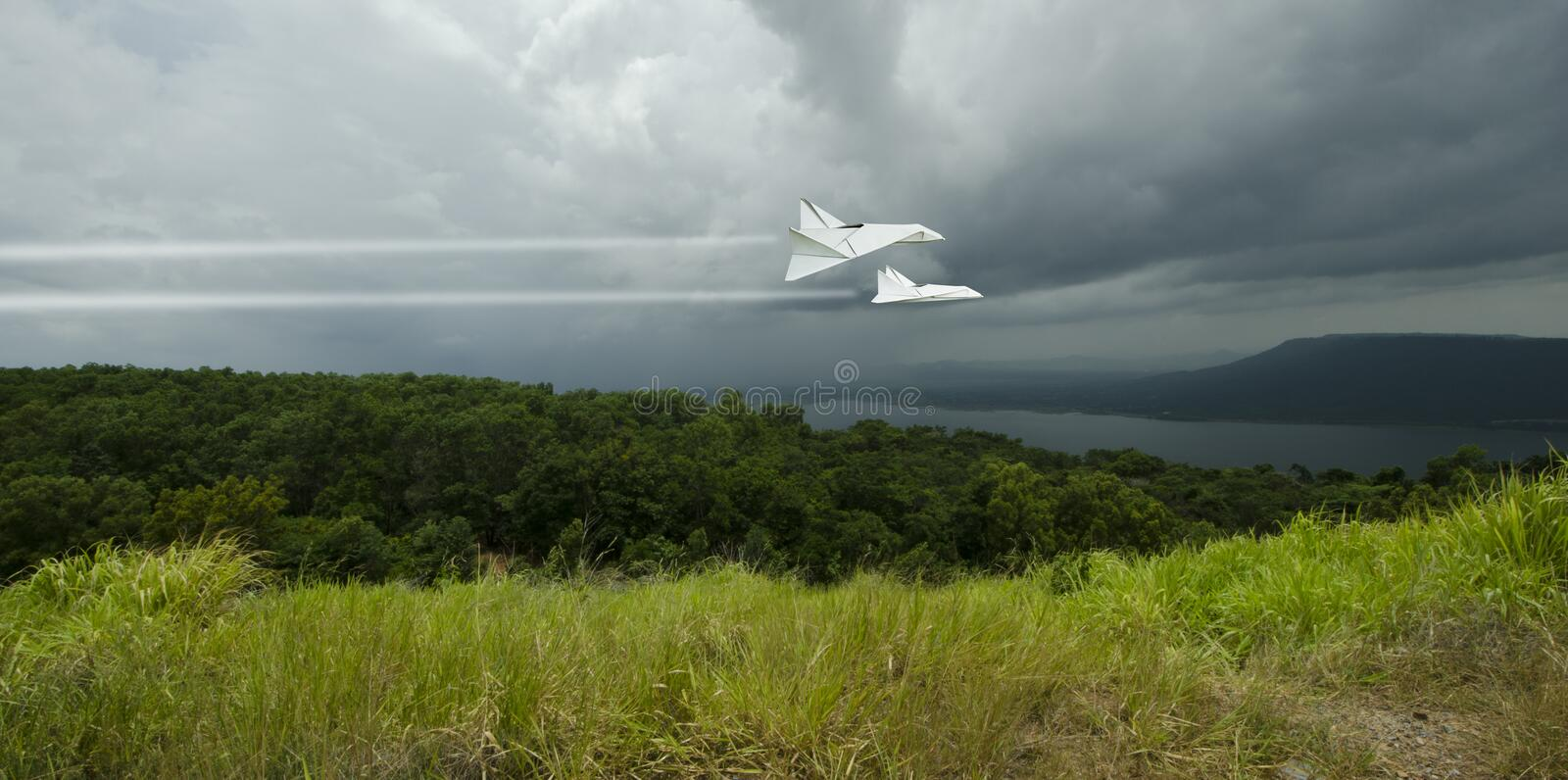 White jets fly high speed through the rainy storm over the forest stock photo
