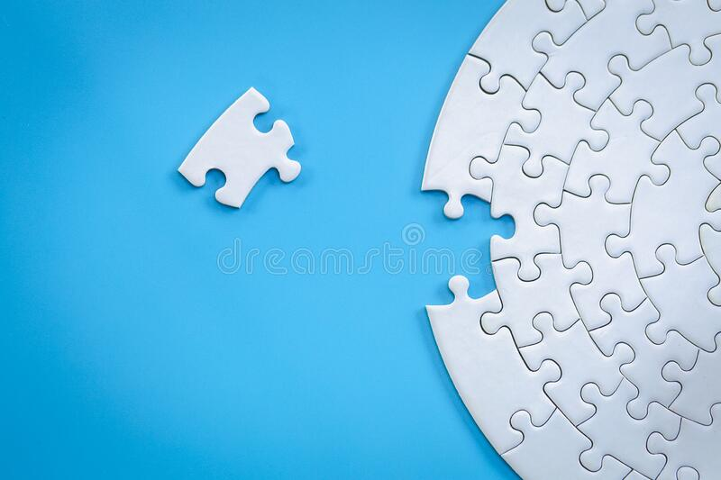 White jigsaw pieces on a blue background, Copy space, Concept image of unfinished task.  missing jigsaw puzzle pieces and business royalty free stock photo