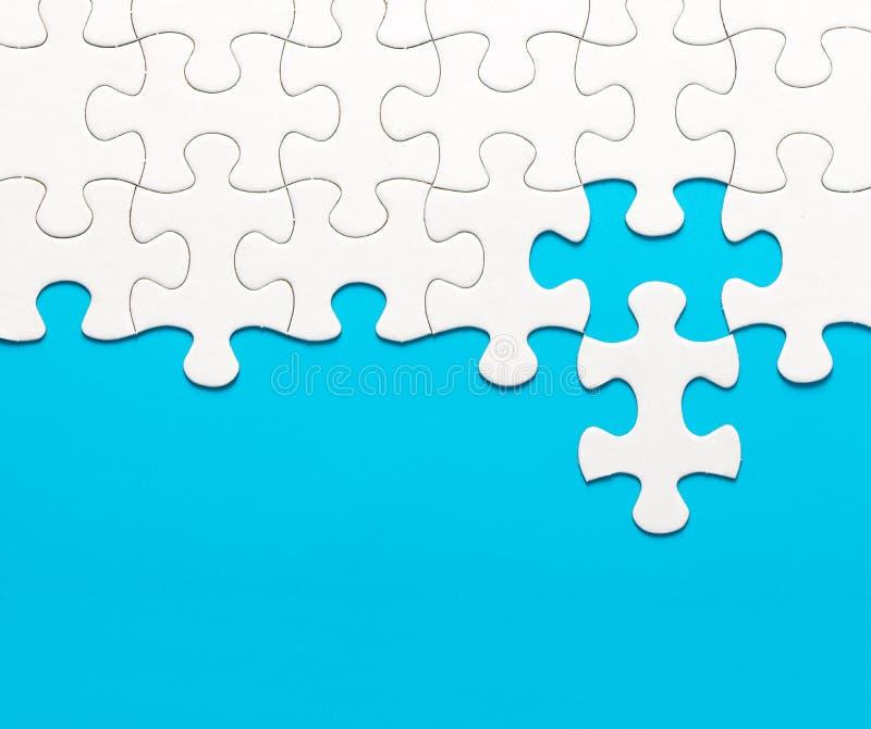 White jigsaw puzzle on blue background royalty free stock image