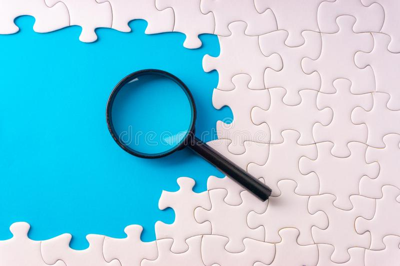 White jigsaw puzzle, Magnifier and missing pieces with selective focus and crop fragment royalty free stock photography