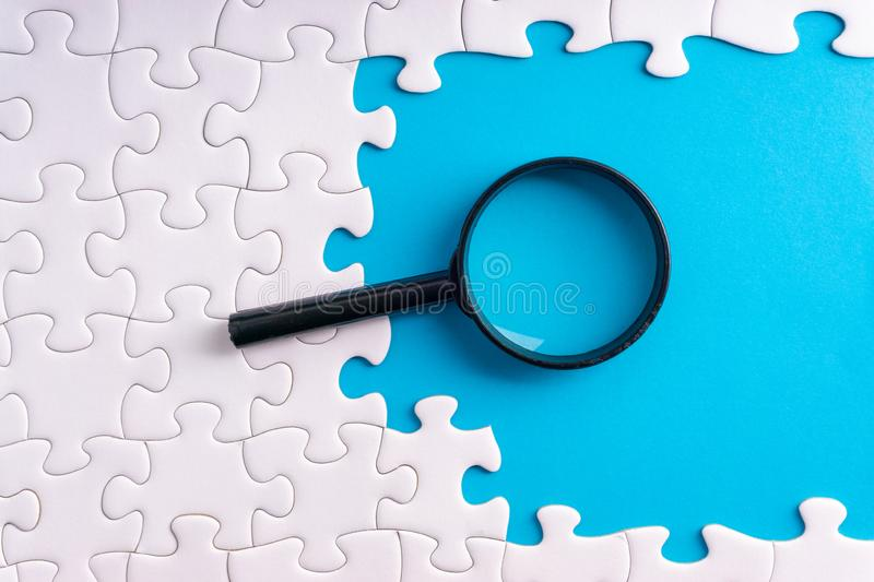 White jigsaw puzzle, Magnifier and missing pieces with selective focus and crop fragment stock image