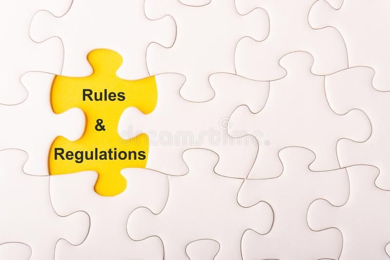 White jigsaw puzzle and missing pieces with words RULES AND REGULATIONS royalty free stock image