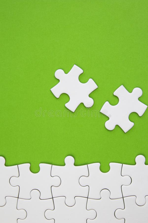 White jigsaw puzzle pieces on green background with negative space stock photo