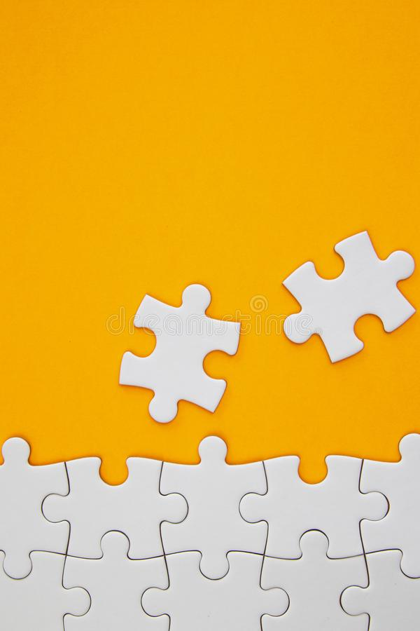 White jigsaw puzzle pieces on orange background with negative space stock image