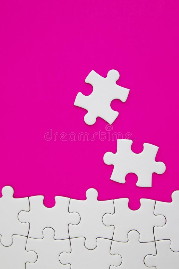 White jigsaw puzzle pieces on pink background with negative space royalty free stock photography