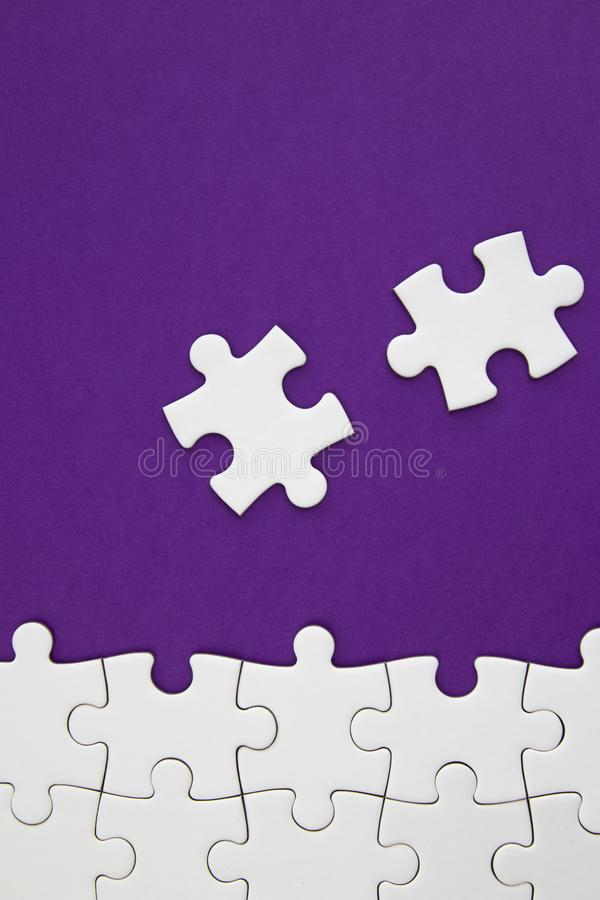 White jigsaw puzzle pieces on purple background with negative space stock images