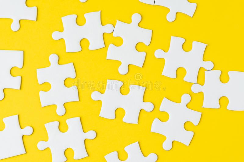 White jigsaw puzzle on solid yellow background metaphor solution to solving business problem, creativity, choice or teamwork. Concept royalty free stock image