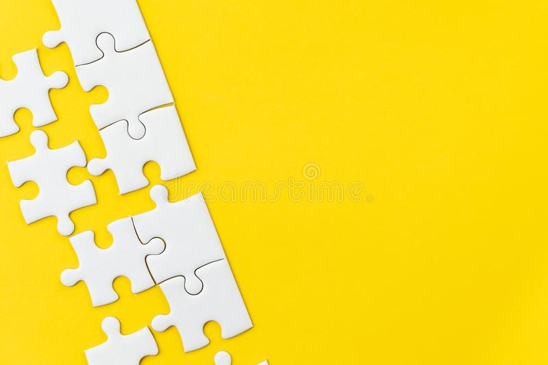 White jigsaw puzzle on vivid yellow background with copy space using for thinking strategy for business solution, teamwork, stock photos