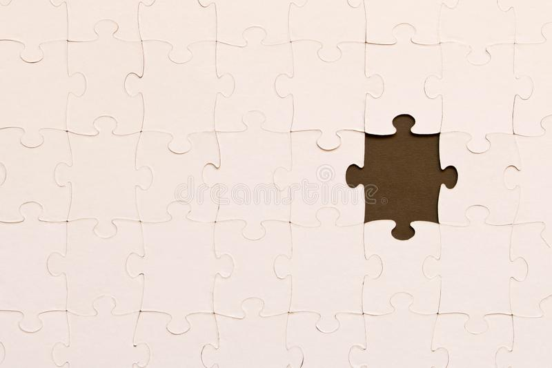 White jigsaw puzzles on black background. The concept of development of thinking. The concept of teamwork.  royalty free stock photos