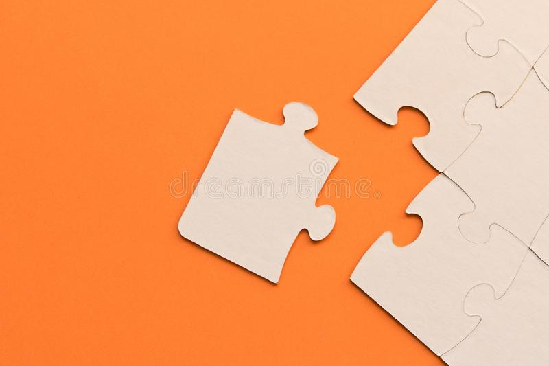 White jigsaw puzzles on orange background. The concept of development of thinking. The concept of teamwork.  stock photography