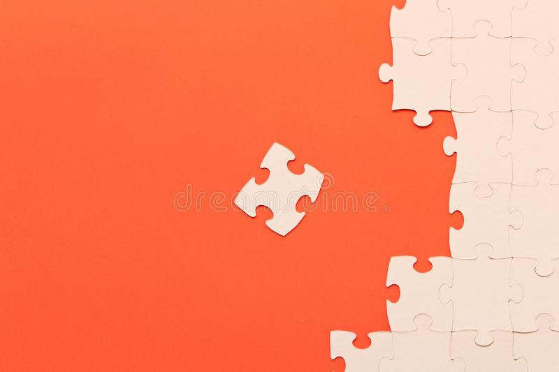 White jigsaw puzzles on red background. The concept of development of thinking.  royalty free stock image