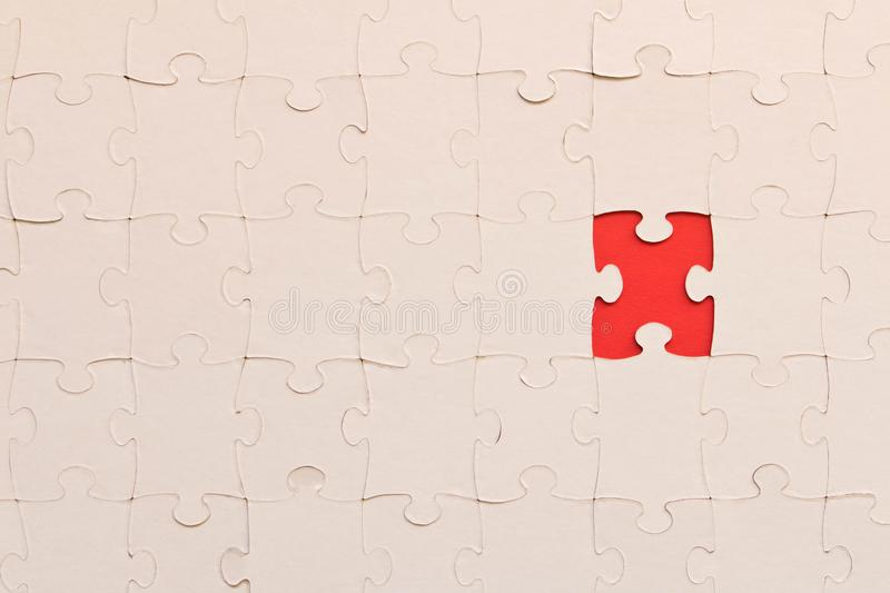 White jigsaw puzzles on red background. The concept of development of thinking. The concept of teamwork.  stock images