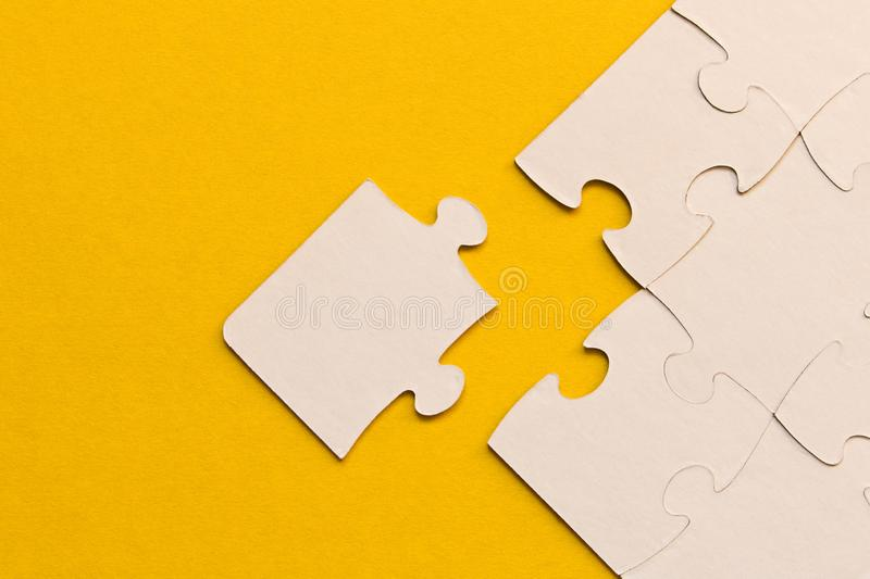 White jigsaw puzzles on yellow background. The concept of development of thinking. The concept of teamwork.  royalty free stock image