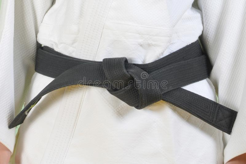 White judo gi. A young martial arts master knots a black belt. stock photo