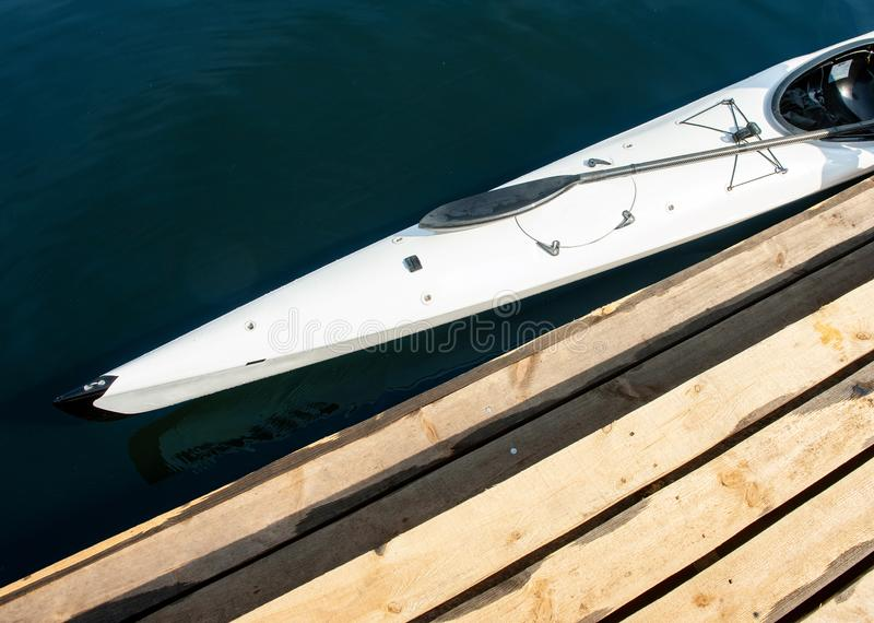 White kayak. Cropped close-up photo of sportive boat. Top view of professional speed canoe placed near boardwalk pier royalty free stock photos