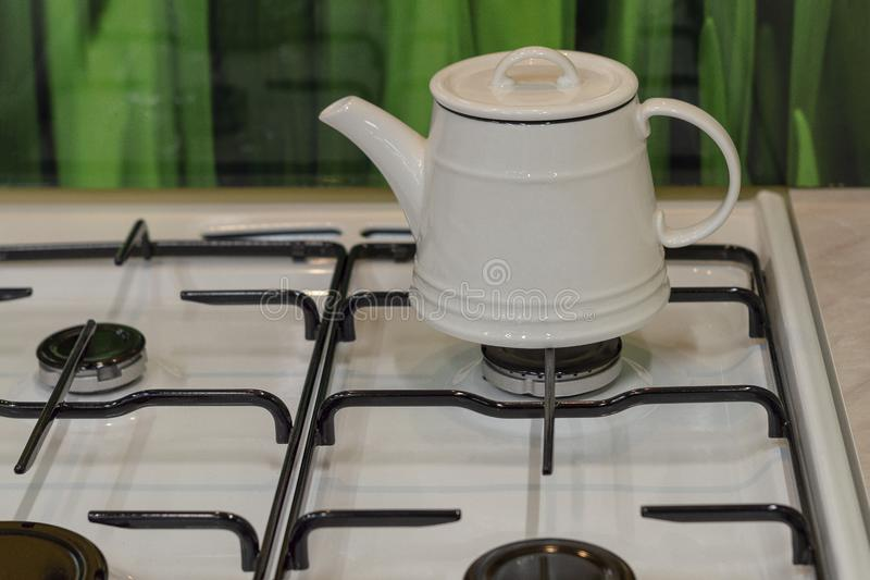 White kettle on a gas stove in the kitchen. stock photography