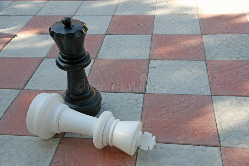 White King in checkmate from Black Queen. Chess pieces with white King in checkmate from Black Queen royalty free stock image