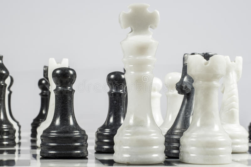 The white king falls under the checkmate of a black pawn. Marble pieces. Elegant chessboard and pieces made of marble. Black pawn gives checkmate to white king stock images