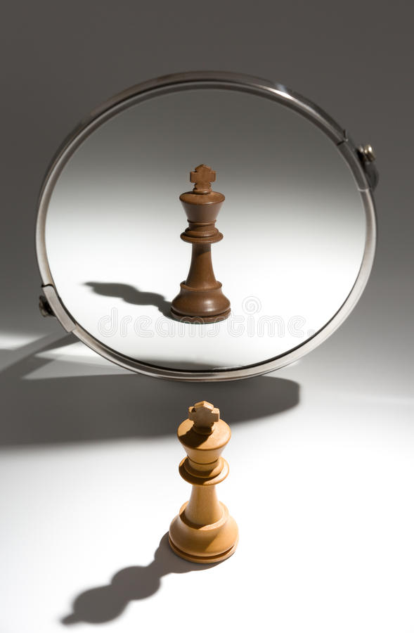 A white king is looking in a mirror to see himself as a black king. royalty free stock photography