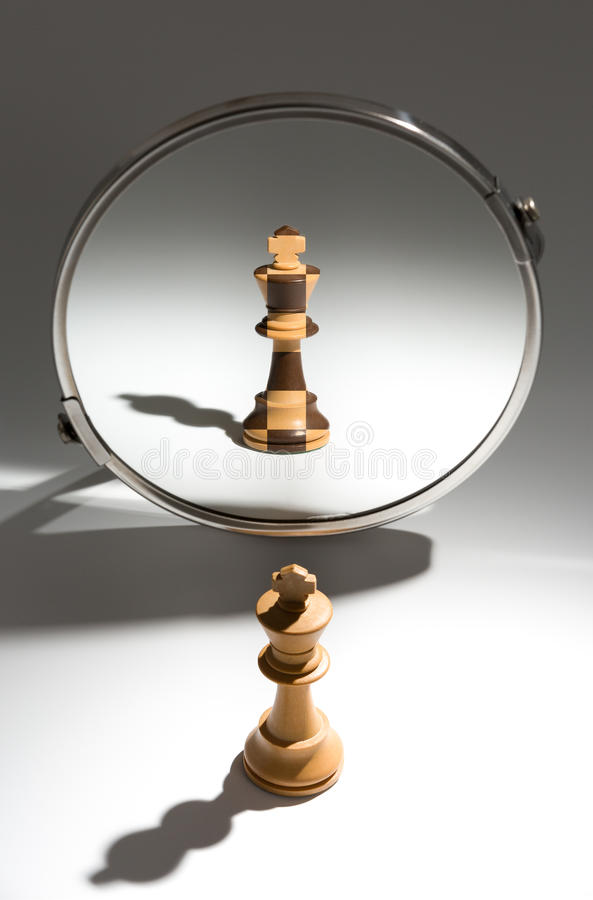 A white king is looking in a mirror to see himself as a black and white colored king. stock photography