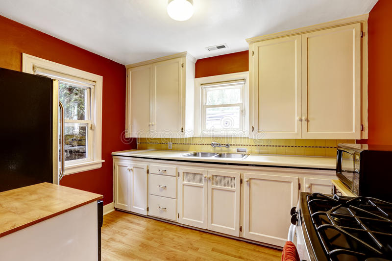 White Kitchen Cabinets With Bright Red Wall Stock Photo