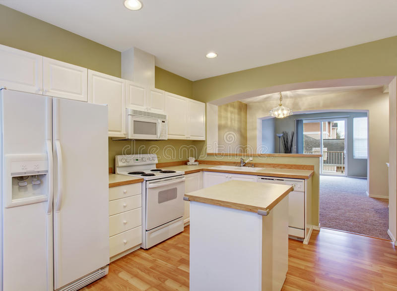 White kitchen cabinets with steel appliances and island,. Hardwood floor royalty free stock image