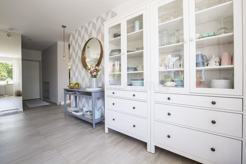 White kitchen cupboard with pastel dishes and blue console table stock photo