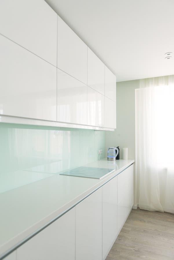 White kitchen in minimalist style. Interior, design theme. White kitchen in minimalist style at apartment. Interior, design theme royalty free stock photo